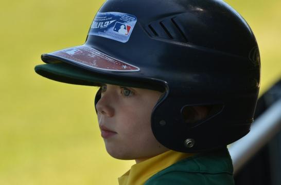 little boy in baseball helmet